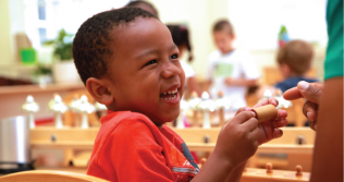 Photo of a small child smiling in a classroom