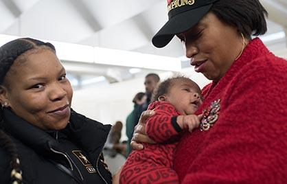 Mayor Bowser holding a baby at Families First event